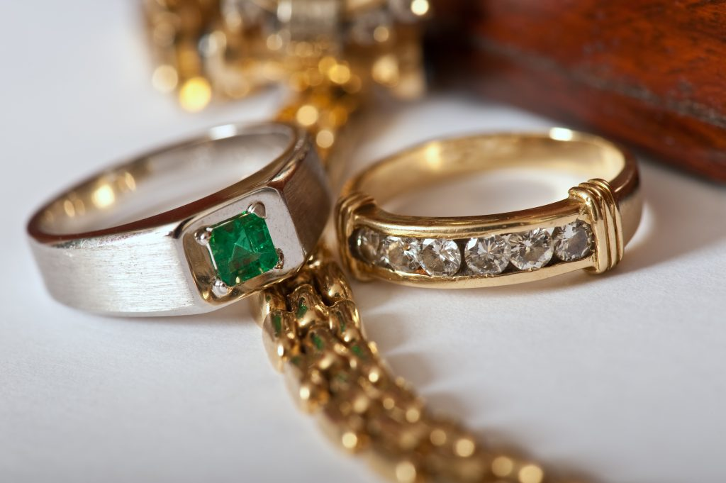 a white gold ring with an emerald stone and a gold ring with diamond by jewllery being valued in newcastle